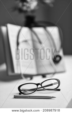 Stethoscope and book on Desk in a medical office black and white poster