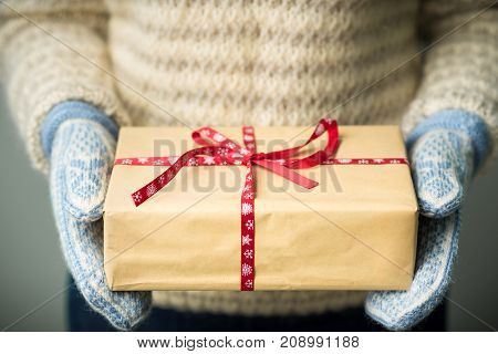 Christmas background. A girl in a warm knitted sweater and mittens is holding a Christmas present. Gifts for men. Merry Christmas. Gift for a girl. Knitted mittens. Knitted dress. Box with gifts.