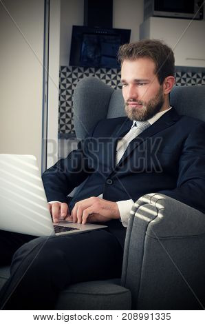 Young Business Man Working From Home With Laptop