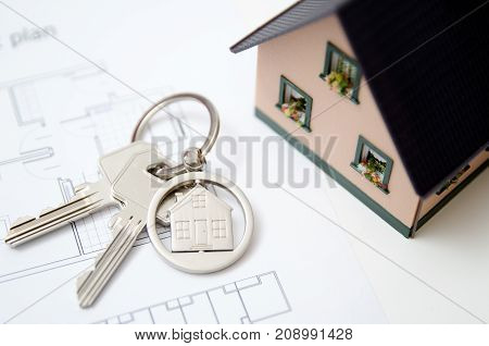House key on a house shaped pendant. Real estate agent concept on white background
