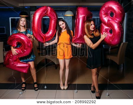 New Year party. Beautiful girls in night club. Merry Christmas 2018, festive mood background. Friends celebrating together, beauty concept
