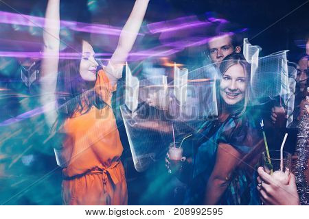 Happy friends dance party in motion. Joyful New Year company in night club, active Christmas celebration. Disco people in blurred colors, modern youth life
