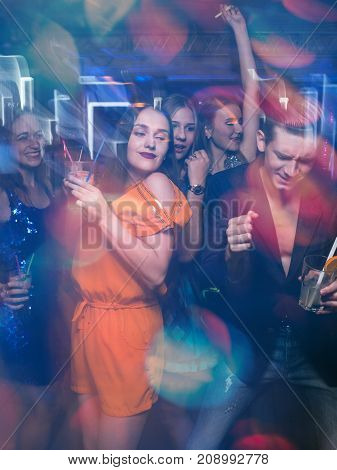 Happy friends dance in motion. Joyful New Year company in night club, active Christmas celebration. Disco party in blurred colors, modern youth life