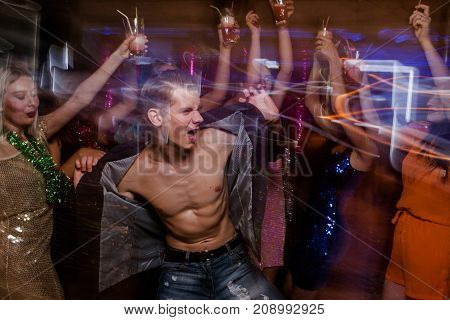 Sexy macho on dance floor. Joyful New Year in night club, positive Christmas celebration in motion. Disco party in blurred colors, modern youth life, pickup concept
