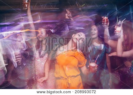 Dance party in night club in blurred motion. Happy friends at Christmas celebration, active New Year company, modern youth life