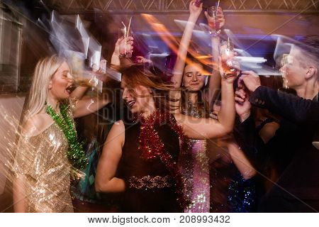 Happy dance at night club in blurred motion. Joyful friends at Christmas discotheque, active New Year company with drinks, modern youth life