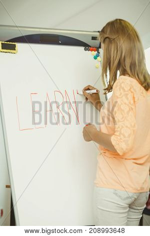 Education knowledge wisdom and learn new things concept - student girl writing Learning word on whiteboard inviting to join