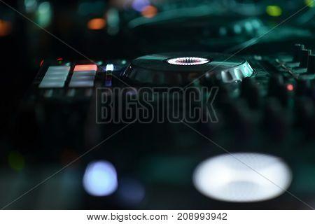 DJ mixer disco illuminated by floodlights at the club
