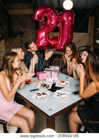 Girl 21st birthday party celebration. Friends company congratulating young female in cafe, modern youth life. Joyful mood, adulthood concept