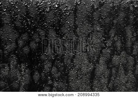 Texture of black iron sheet with streaks and drops of water.