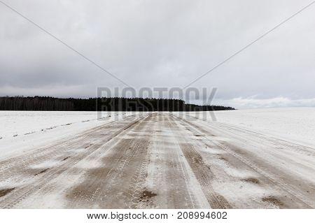 not asphalt road in the countryside. On the surface there are traces of cars on the dirt of yellow snow from the mud. Cloudy sky and forest in the background. winter landscape