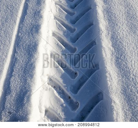 trail of the tractor on white snow. photo close-up in winter, view from above and at an angle