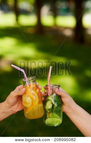 Group of people celebrate with detox juice cocktailss on green nature background witn free space. Diet on the go, well being and weight loss, superfoods, health, vegetarian food concept
