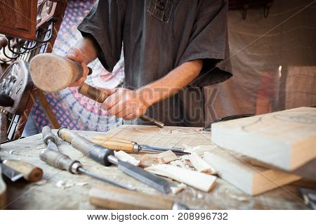 Wood craftsman with various hand tools working
