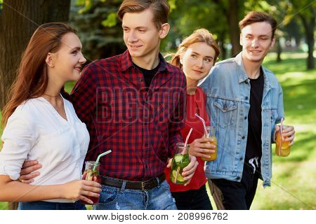 Group of young people with detox cocktails spend time together at summer. Friendship, youth lifestyle, vegetarian diet, fitness food on the go, successful weight loss concept