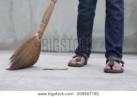 A Man Sweeping The Floor. Legs View.