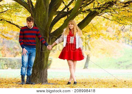 Young Couple Meet In Park On Date Holding Hands.