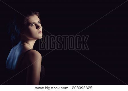 beautiful sad young woman on black background with copy space looking over shoulder at camera