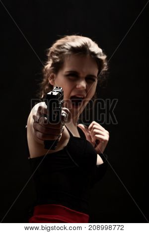 girl with gun on black background aiming at camera screaming