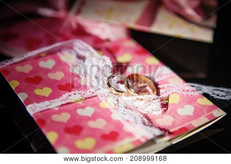 two golden wedding rings on a pink box, wedding rings background concept