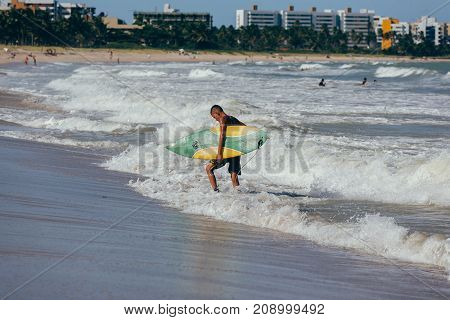 Cabedelo, Paraiba, Brazil - October 15, 2017 - A Surfer With His Surfboard On The Beach