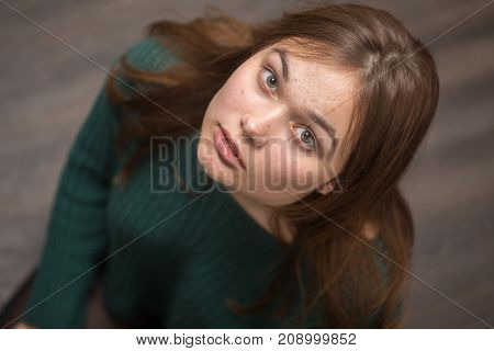 sad beautiful young woman with pimple skin looking up at camera