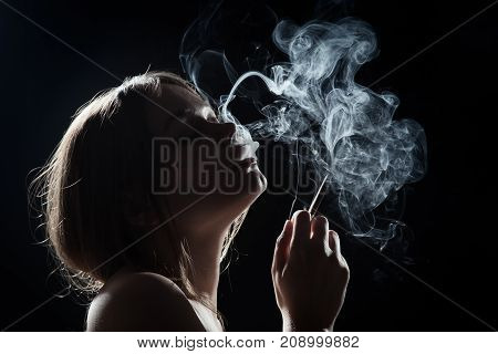 young woman smoking cigarette on black background