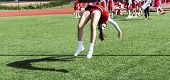 A cheerleader is practicing back flips while getting ready for homecoming at a local high school. poster