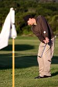 Golfer chipping the ball towards the flag on the green poster