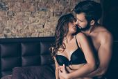 Beautiful half naked brunet young couple is embracing in the bed room about to have sex so tender romantic tempting sensual. True love and feelings gentle touch and caress poster
