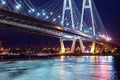 Big Obukhovsky bridge. Cable-stayed fixed bridge across Neva river in St. Petersburg. One of longest road bridges in Russia on autumn night. Bridge brightly lit road lights reflected in water poster