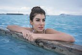Hot girl in a white swimsuit holds her hands on a wooden crossbeam in the geothermal pool on the background of the cloudy sky outdoors in Iceland. She looks to the side with parted lips. Horizontal. poster
