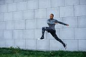 Freeze action shot of sturdy healthy young African American male athlete in trendy sportswear doing high jumps outdoors at blank grey wall. Strenght power endurance determination and stamina poster