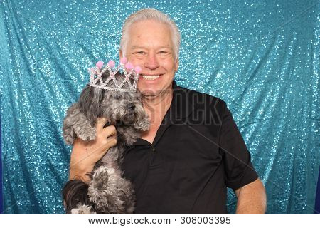 Man in a Photo Booth with a Dog. A man poses and smiles while in a photo booth with blue sequin drapes with a small dog. Photo Booths are fun for everyone even dogs.
