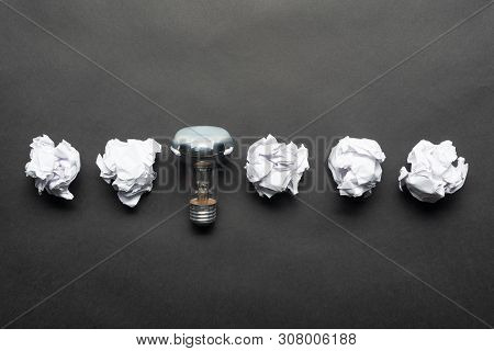 Lightbulb And Crumpled White Paper Balls On Black Background. Successful Solution Of Problem. Think