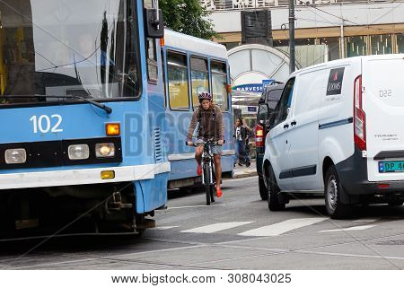 Oslo, Norway - June 20, 2019: One Bicycle Rider Betweeen The Streetcar And And Car At The Oslo City