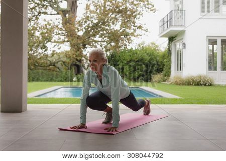 Front view of determined active senior Caucasian woman doing yoga on exercise mat in the porch at home