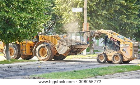Ukraine, Shostka - June 14, 2019: One Tractor Pours Hot Asphalt Into Another, Construction Of A New