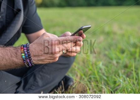 Caucasian Male Texting On Cell, Sitting On Grass Outside With Rainbow Bracelets.
