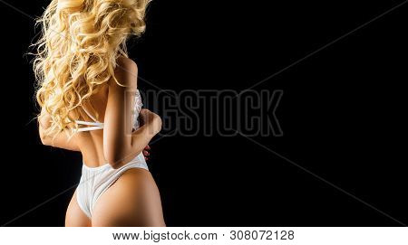 Blonde With Curly Hair And Copy Space. Black Background. Sexy Concept. Advertising Of Underwear For