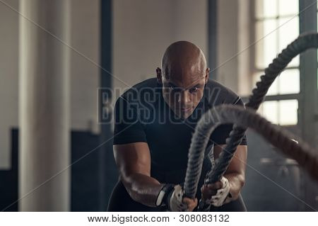 Man in sportswear doing battle ropes functional training at gym. Determined trainer making waves with ropes while exercising strength. Athlete working out with battle rope at industrial gym.