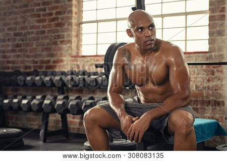 Shirtless african sportsman resting after training at gym. Mature muscular athletic man sitting on bench after working out. Tired and exhausted guy sweating and taking a breath after heavy workout.