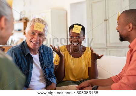 Group of multiethnic mature friends playing guess sticky head game at home. Men and smiling women enjoying charades game session. African woman trying to make her friend guess the character.