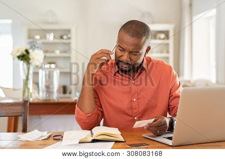 Mature man paying bills while talking on phone. Thoughtful man at home in conversation over smartphone while checking receipts. Worried african man discussing expenses over phone with bank insurance.