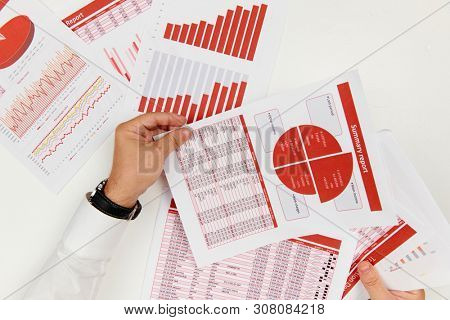 Business reports, data tables and charts - directly above view of office table workspace.