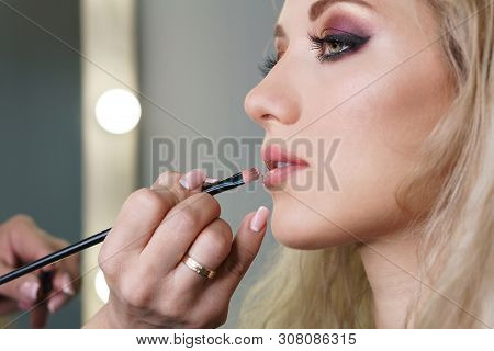 Makeup Artist Working In Make-up Studio, Causing Makeup To Face Of Women Clients. Makeup Artist Appl