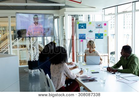 Front view of diverse business people attending video conference at conference room in a modern office