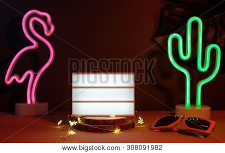 Summer Items With Flamingo, Cactus, Sunglasses And Blank Light Box With Neon Pink And Blue Light On