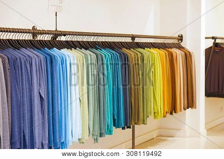 Fashionable Clothing On Hangers In Shop. Sport Of T Shirts Are Hanging On Clothes Hanger , Colorful