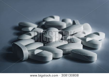 Closeup of many white prescription drugs, medicine tablets or vitamin pills in a pile - Concept of healthcare, opioids addiction, medicament abuse or medication treatment